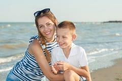 Fostra och hennes son som har gyckel på stranden Royaltyfri Foto