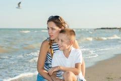 Fostra och hennes son som har gyckel på stranden Royaltyfria Bilder