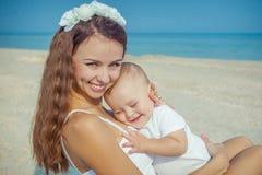 Fostra och hennes son som har gyckel på stranden Arkivbilder