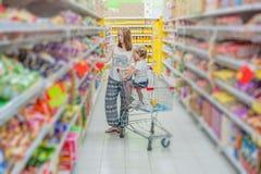 Fostra och hennes sonköpandemat på en supermarket arkivfoton