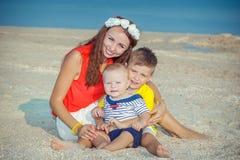 Fostra och hennes två söner som har gyckel på stranden Arkivfoto