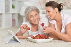 Fostra och hennes vuxna dotter som äter nya jordgubbar Royaltyfri Foto