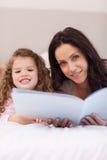 Fostra och läs- läggdagsberättelser för dottern tillsammans Royaltyfri Fotografi