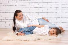 Fostra, och dottern som ligger på en vit, pälsfodrar Arkivfoton