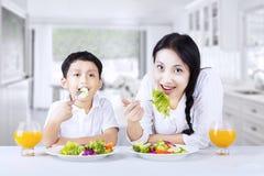 Asiatisk familj som hemma eathing sund sallad Arkivfoton
