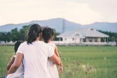 Fostra och två asiatiska flickor för litet barn som ser huset Royaltyfria Bilder