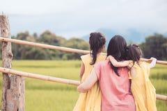 Fostra och två asiatiska flickor för litet barn som ser naturen Arkivfoto