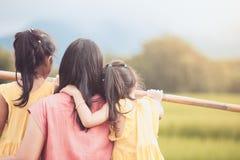 Fostra och två asiatiska flickor för litet barn som ser naturen Arkivbilder