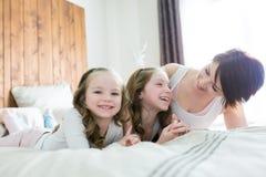 Fostra och två barn i sovrummet på sängen arkivbilder
