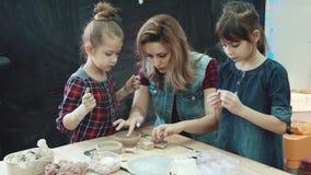 Fostra och två döttrar i en idérik grupp i krukmakeriseminariet barn gör former ut ur lera stock video