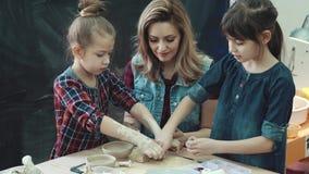 Fostra och två döttrar i en idérik grupp i krukmakeriseminariet barn gör former ut ur lera arkivfilmer