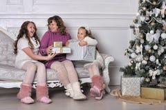 Fostra och två döttrar med gåvor på en soffa arkivfoton