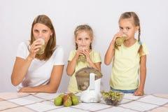 Fostra och två döttrar som dricker nytt gjord fruktsaft Royaltyfri Bild