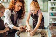 Fostra och två rödhårig mandöttrar som göras lerakoppen med krukmakeri för att rulla arkivfoton