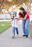 Fostra undervisningdottern för att rida sparkcykeln Royaltyfri Fotografi
