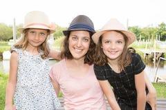 Fostra utomhus- nportrait med dottern för två flickor med sugrörhatten nära sjöfloden i vår Royaltyfri Bild