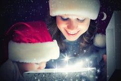 Fostrar behandla som ett barn den magiska gåvaasken för jul och en lycklig familj och Fotografering för Bildbyråer
