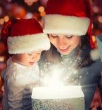 Fostrar behandla som ett barn den magiska gåvaasken för jul och en lycklig familj och Arkivbild