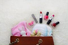 Fostrar handväskan med objekt för att att bry sig för barn royaltyfri foto