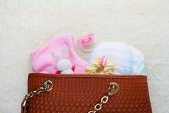 Fostrar handväskan med objekt för att att bry sig för barn arkivfoton