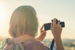 Fotógrafo árabe de la mujer en una bufanda que toma la imagen usando cámara en el fondo de la puesta del sol Concepto Halal del v fotos de archivo libres de regalías