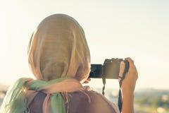 Fotógrafo árabe de la mujer en una bufanda que toma la imagen usando cámara en el fondo de la puesta del sol Concepto Halal del v imagenes de archivo