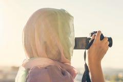 Fotógrafo árabe de la mujer en una bufanda que toma la imagen usando cámara en el fondo de la puesta del sol Concepto Halal del v fotos de archivo