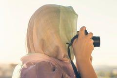 Fotógrafo árabe de la mujer en una bufanda que toma la imagen usando cámara en el fondo de la puesta del sol Concepto Halal del v imagen de archivo