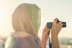 Fotógrafo árabe de la mujer en una bufanda que toma la imagen usando cámara en el fondo de la puesta del sol Concepto Halal del v fotografía de archivo