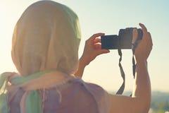 Fotógrafo árabe de la mujer en una bufanda que toma la imagen usando cámara en el fondo de la puesta del sol Concepto Halal del v foto de archivo libre de regalías