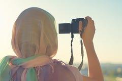 Fotógrafo árabe de la mujer en una bufanda que toma la imagen usando cámara en el fondo de la puesta del sol Concepto Halal del v fotografía de archivo libre de regalías
