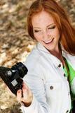 Fotógrafo agradable de la muchacha que toma el selfe en parque del otoño Imagen de archivo