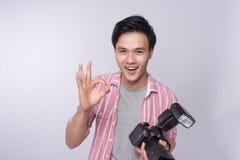 Fotógrafo asiático novo que guarda a câmara digital, ao trabalhar i fotografia de stock