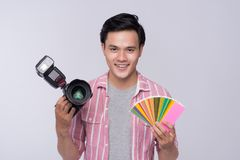 Fotógrafo asiático novo que guarda a câmara digital, ao trabalhar i imagem de stock