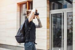 Fotógrafo atractivo del hombre que hace las fotos del edificio moderno foto de archivo