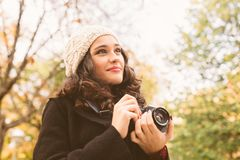 Fotógrafo bonito que olha árvores do outono Fotografia de Stock