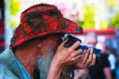 Fotógrafo com barba e chapéu que olha o visor da câmera Imagens de Stock