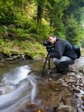 Fotógrafo com a câmera no tripé Fotografia de Stock