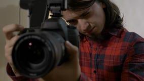 Fotógrafo com o cabelo escuro que olha através da lente objetiva de sua câmara digital em um estúdio profissional e que toma foto vídeos de arquivo