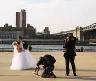 Fotógrafo com os pares do recém-casado do tiro do grupo sob a ponte de Brooklyn imagens de stock