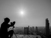 Fotógrafo con el trípode que toma la foto en el tejado del edificio, Bangk fotografía de archivo