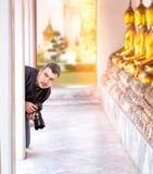 Fotógrafo con la cámara digital en el templo de Buda Fotos de archivo libres de regalías