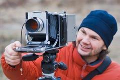 Fotógrafo con viejo tirar de la cámara al aire libre. Fotos de archivo libres de regalías