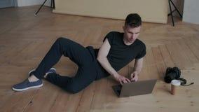 Fotógrafo criativo à moda que retoca imagens em seu portátil na posição do conforto ao encontrar-se sobre o assoalho desenhador video estoque