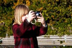 Fotógrafo da criança que fotografa tomando a foto Imagens de Stock Royalty Free