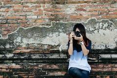 Fotógrafo da jovem mulher do retrato da vista dianteira que guarda a câmera e Fotos de Stock Royalty Free