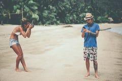 Fotógrafo da jovem mulher para fazer fotos do homem novo na praia foto de stock royalty free