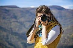 Fotógrafo da jovem mulher que toma a foto de uma montanha bonita Fotos de Stock