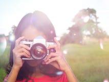 Fotógrafo da menina que cobre sua cara com a câmera fotografia de stock