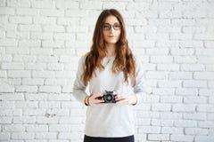 Fotógrafo da mulher que guarda uma câmera do filme nas mãos imagem de stock